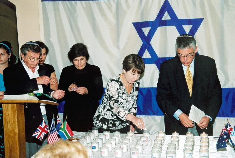Kupiškio žydų palikuonys uždega žvakutes prie savo sušaudytų protėvių atminimo lentos Kupiškio viešojoje bibliotekoje. Pirmas iš kairės – Normanas Mejeris, dešinėje – Harvis Šerzeras. KUPIŠKIO ETNOGRAFIJOS MUZIEJAUS ARCHYVO nuotr.